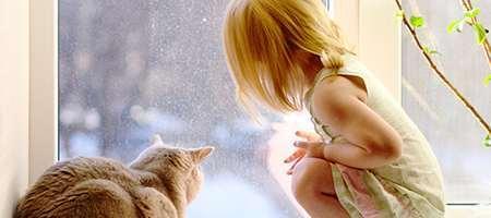 Mädchen mit Katze am Fenster
